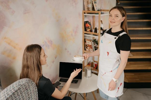 Ein weiblicher barista mit piercing hält einem mädchen in einem café einen latte hin. eine junge frau mit langen haaren, die ferngesteuert an einem laptop arbeitet, hält soziale distanz und holt sich eine tasse kaffee in einem café.
