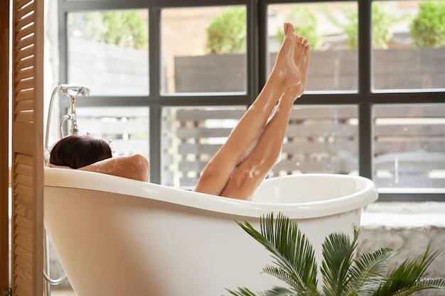 Ein weiblicher genuss liegt in einer weißen badewanne und schaut durch ein großes fenster auf die straße. rückansicht erschossen