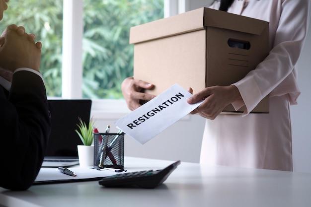 Ein weiblicher geschäftsmann, der eine braune pappschachtel hält und schickt dem management ein kündigungsschreiben. umzug von arbeitsplätzen und offenen stellen