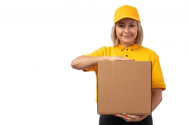 Ein weiblicher kurier der vorderansicht im gelben hemd gelbe kappe, die paket hält, das auf weiß lächelt