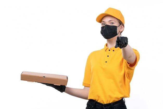 Ein weiblicher kurier der vorderansicht in den gelben einheitlichen schwarzen handschuhen und in der schwarzen maske, die lebensmittelbox zeigt