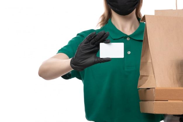 Ein weiblicher kurier der vorderansicht in den grünen schwarzen handschuhen der grünen uniform und in der schwarzen maske, die lebensmittellieferungspakete liefern liefert