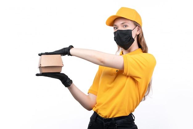 Ein weiblicher kurier der vorderansicht in den schwarzen handschuhen der gelben uniform und der schwarzen maske, die nahrungsmittelpaket hält