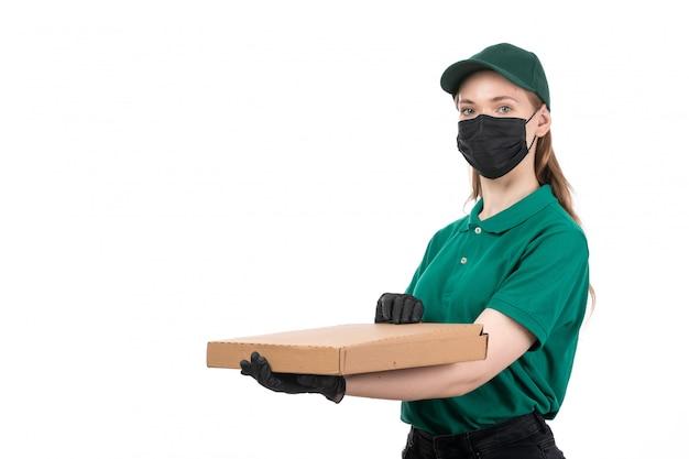 Ein weiblicher kurier der vorderansicht in den schwarzen handschuhen der grünen uniform und in der schwarzen maske, die lebensmittellieferungspaket hält