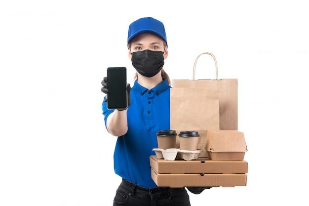 Ein weiblicher kurier der vorderansicht in den schwarzen schwarzen handschuhen der blauen uniform und der schwarzen maske, die lebensmittel-lieferpakete halten