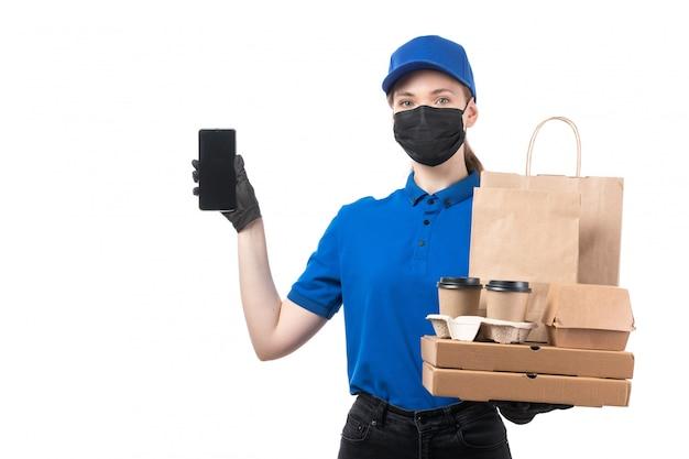 Ein weiblicher kurier der vorderansicht in den schwarzen schwarzen handschuhen der blauen uniform und der schwarzen maske, die lebensmittel-lieferpakete und smartphone halten