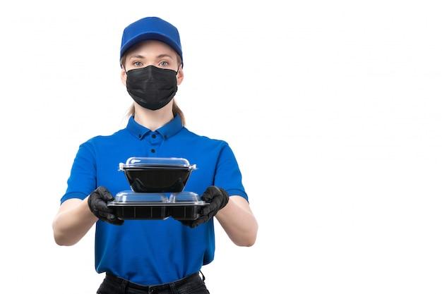 Ein weiblicher kurier der vorderansicht in den schwarzen schwarzen handschuhen der blauen uniform und in der schwarzen maske, die nahrungsschalen hält
