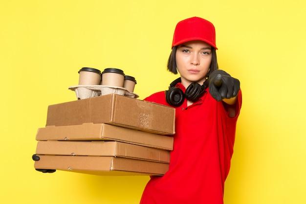 Ein weiblicher kurier der vorderansicht in den schwarzen schwarzen handschuhen der roten uniform und der roten kappe, die nahrungsmittelkästen hält