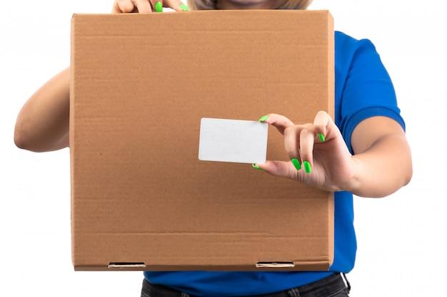 Ein weiblicher kurier der vorderansicht in der blauen uniform, die lebensmittel-lieferpaket und weiße karte hält