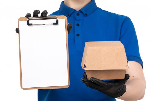 Ein weiblicher kurier der vorderansicht in der blauen uniformschwarzmaske und in den handschuhen, die lebensmittel-lieferpaket und notizblock halten