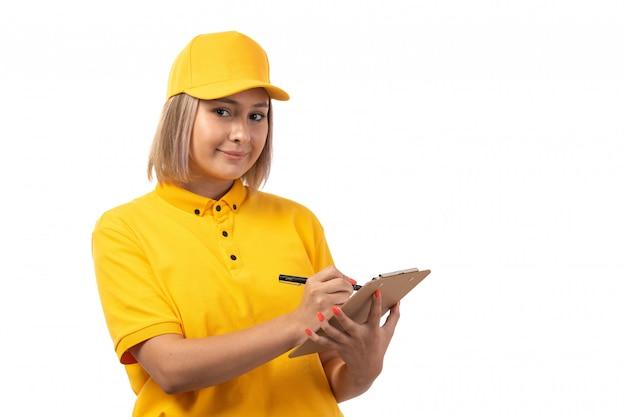 Ein weiblicher kurier der vorderansicht in der gelben kappe der schwarzen jeans der gelben kappe lächelnd, die bestellungen auf weiß aufschreibend