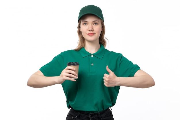 Ein weiblicher kurier der vorderansicht in der grünen uniform, die kaffeetasse hält und auf weiß lächelt