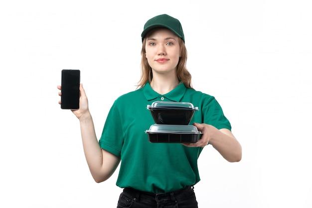 Ein weiblicher kurier der vorderansicht in der grünen uniform, die smartphone und schüsseln mit essen hält