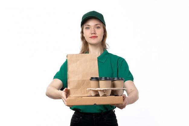 Ein weiblicher kurier der vorderansicht in der grünen uniform lächelnd, die kaffeetassen-lebensmittelpakete hält