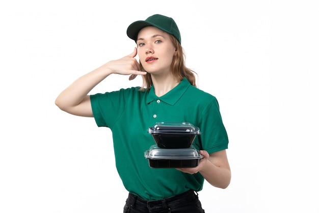 Ein weiblicher kurier der vorderansicht in der grünen uniform lächelnd, die nahrungsmittelschalen hält