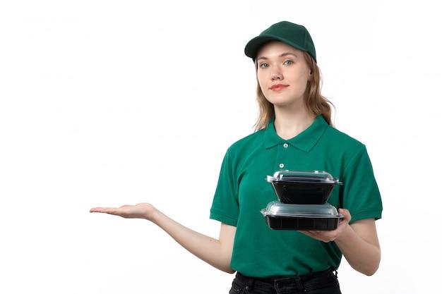 Ein weiblicher kurier der vorderansicht in der grünen uniform lächelnd, die schwarze schalen mit essen hält