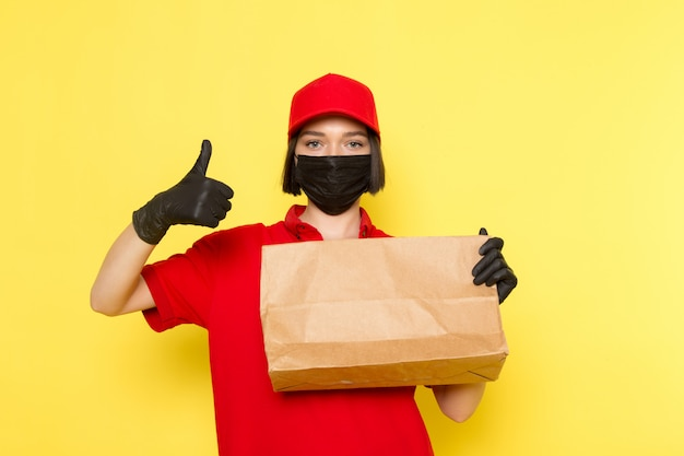 Ein weiblicher kurier der vorderansicht in der schwarzen maske der roten uniform schwarzen handschuhen und der roten kappe, die lebensmittelpaket hält