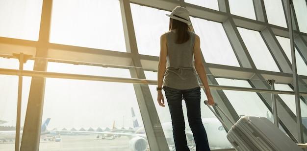 Ein weiblicher tourist geht in einen rollstuhl in einem flughafen, um mit dem flugzeug zu reisen. reise-konzept