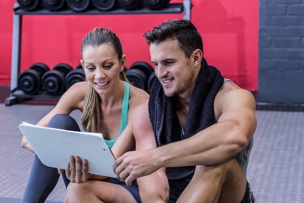 Ein weiblicher trainer, der richtlinien mit klemmbrett erklärt