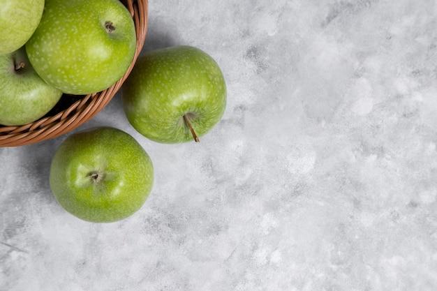 Ein weidenkorb mit frischen grünen äpfeln auf stein