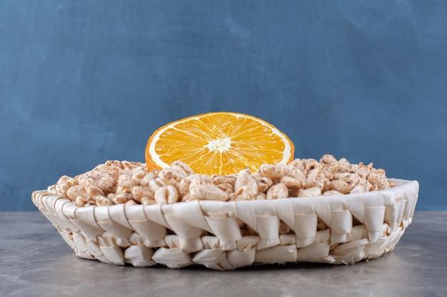 Ein weidenkorb mit gesunden knusprigen reis-frühstückszerealien mit einer orangenscheibe.