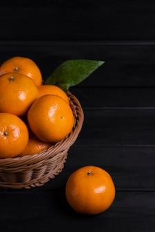 Ein weidenkorb voller frischer mandarinenfrüchte mit blättern auf einem dunklen holztisch. hochwertiges foto