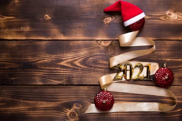 Ein weihnachtsbaum aus goldband mit den nummern 2021 ist mit roten luftballons auf dunklem holzhintergrund geschmückt. flach liegen. platz für text. neues jahr, weihnachtsmütze.