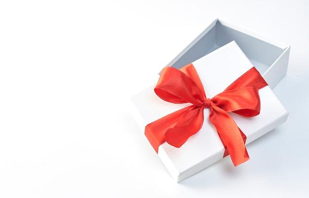 Ein weihnachtsgeschenk im weißen packpapier und in den roten bändern