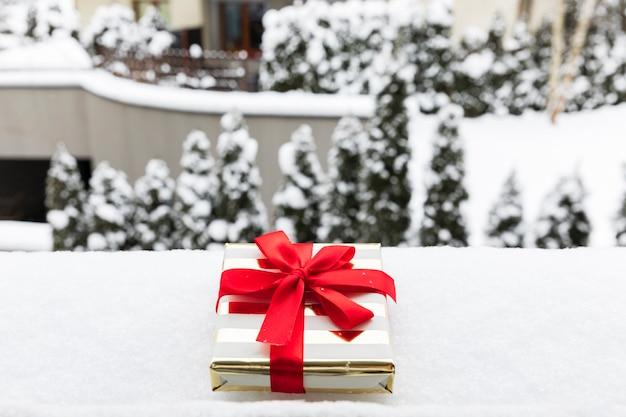 Ein weihnachtsgeschenk in einem festlichen paket auf dem schnee. c.