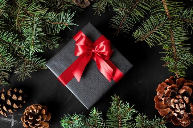 Ein weihnachtsgeschenk in schwarzem papier, das mit einem roten band auf einem hintergrund von tannenzweigen und zapfen gebunden ist