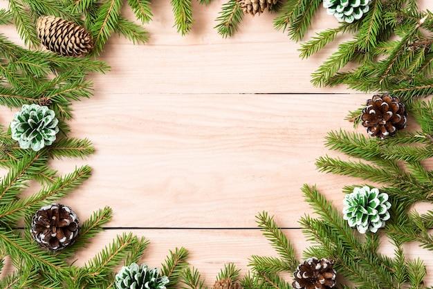 Ein weihnachtskonzept von zweigen, zapfen und sternen wird auf einem holztisch zusammengestellt.