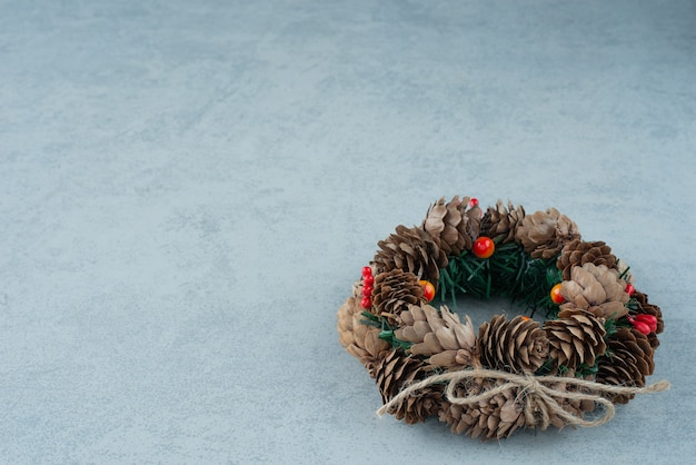 Ein weihnachtskranz aus tannenzapfen auf marmorhintergrund. hochwertiges foto