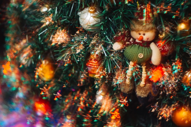 Ein weihnachtsspielzeug in form eines schneemanns hängt an einem künstlichen weihnachtsbaum mit bunten hellen lichtern.
