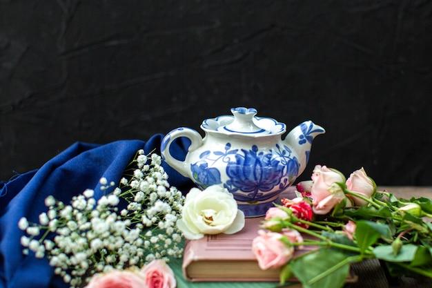 Ein weiß-blauer wasserkocher aus der nähe von oben um blaues gewebe und verschiedenfarbige rosen auf dem dunklen boden
