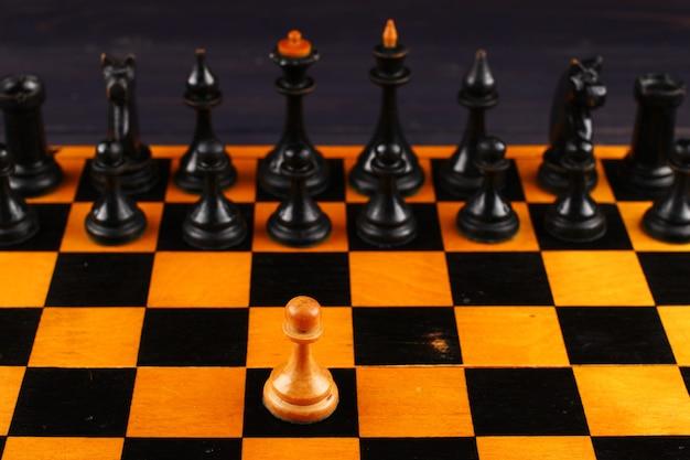 Ein weißer bauer gegen schwarze schachfiguren