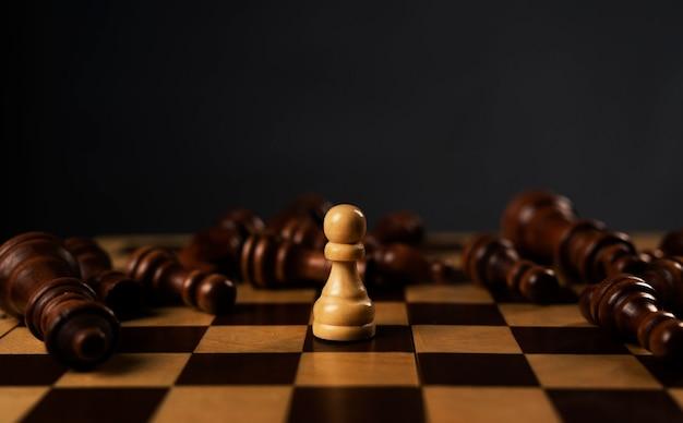 Ein weißer bauer gewinnt unter den gefallenen schwarzen schachfiguren auf dem schachbrett.