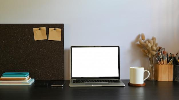 Ein weißer computer-laptop mit leerem bildschirm stellt einen schwarzen schreibtisch auf, der von zubehör umgeben ist