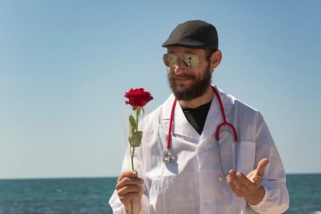 Ein weißer glücklicher bärtiger jüdischer arzt mit kaukasischem aussehen riecht eine rote rose und lächelt fröhlich. amerikanischer russischer mann mit stethoskop, sonnenbrille, mütze, mantel gegen blauen himmel, rote rose haltend