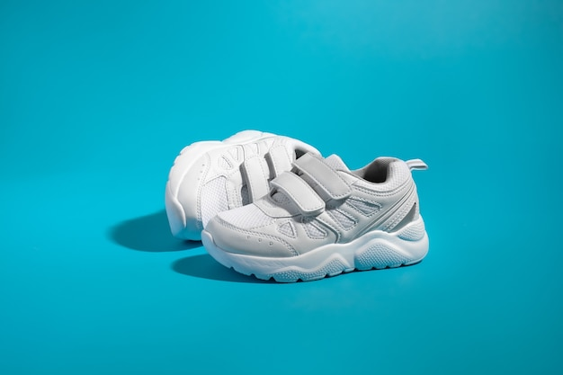Ein weißer kindersneaker mit klettverschlüssen zum bequemen beschuhen steht vor dem anderen liegend...