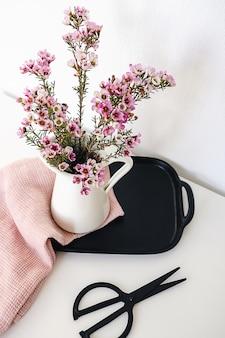 Ein weißer krug mit lila blumenstrauß auf einem schwarzen tablett mit rosa handtuch und schere im alten stil, die auf einem tisch von oben gesehen liegen