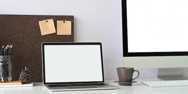 Ein weißer laptop mit leerem bildschirm stellt einen weißen schreibtisch auf, der von bürogeräten umgeben ist.