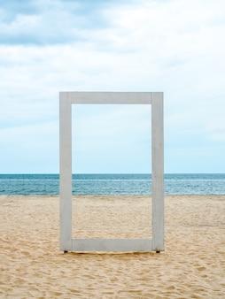 Ein weißer leerer holzrahmen, der durch die seelandschaft, den strand, das meer und den blauen himmel sehen kann, minimaler stil, vertikaler stil.
