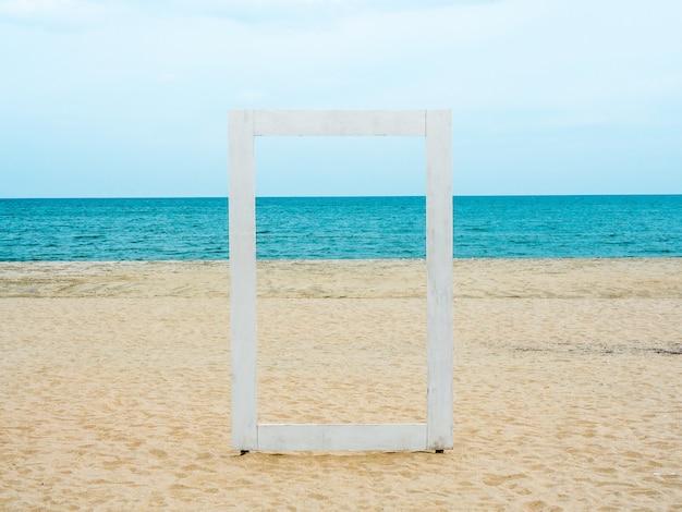 Ein weißer leerer holzrahmen, der durch die seelandschaft, den strand, das meer und den blauen himmel sehen kann