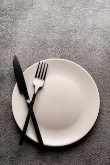 Ein weißer leerer teller auf einem grauen tisch und eine gabel und ein messer. konzept für ein restaurant oder menü flach legen copyspace