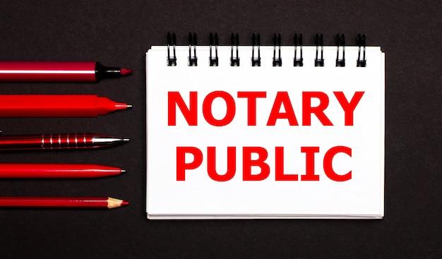 Ein weißer notizblock mit dem text notary public, geschrieben auf einem weißen notizblock neben roten kugelschreibern, bleistiften und markern auf schwarzem hintergrund.