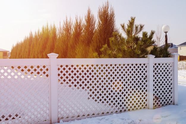 Ein weißer plastikzaun in einem modernen cottage-dorf an einem klaren wintertag bei sonnenuntergang