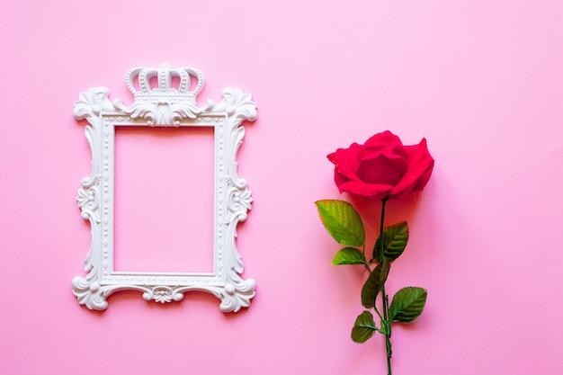 Ein weißer rahmen und herzen über rosa hintergrund und ein blumenstrauß von roten rosen