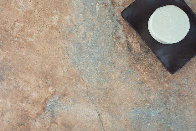 Ein weißer runder käse auf dunklem teller auf marmortisch.