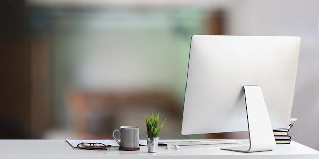 Ein weißer schreibtisch ist von einem computermonitor und bürogeräten umgeben