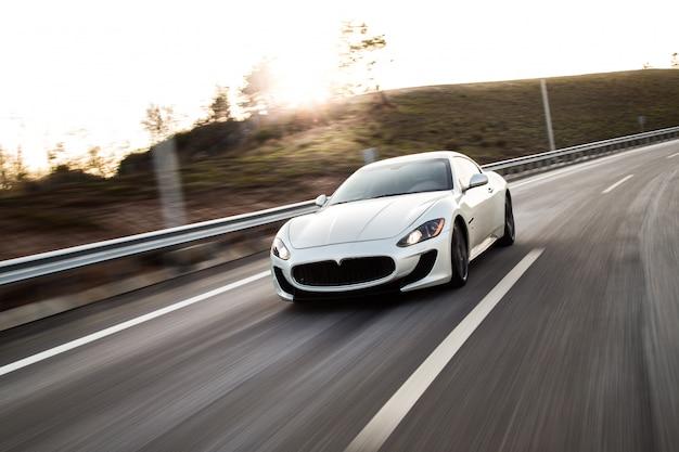 Ein weißer sportwagen, der mit hoher geschwindigkeit auf die straße fährt.